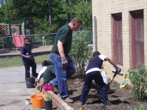 A Riverine volunteer helps students prepare garden beds for planting